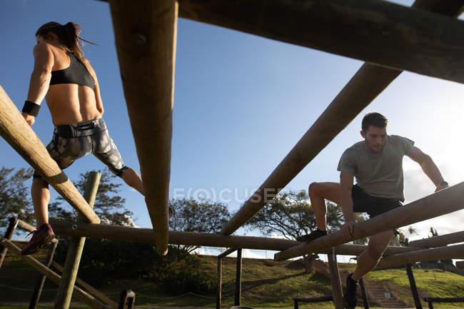 Vista trasera de una joven mujer caucásica y vista frontal de un joven caucásico trepando a través de vigas en un marco de escalada en un gimnasio al aire libre durante una sesión de entrenamiento de bootcamp - foto de stock