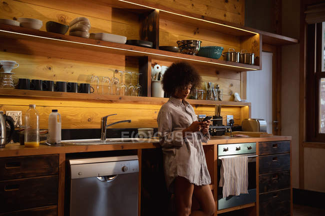 Side view of a young mixed race woman wearing a shirt standing using a smartphone at home in her kitchen — Stock Photo