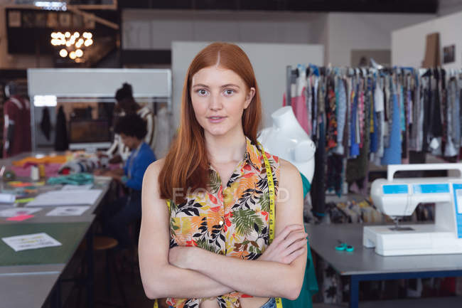 Front view of a young Caucasian female fashion student standing with arms crossed in a studio at fashion college — стокове фото