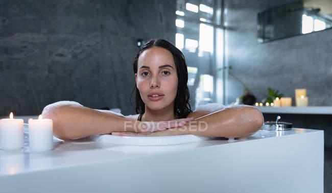 Портрет молодой кавказской брюнетки, сидящей в пенной ванне с зажженными свечами на краю, наклоняющейся сбоку и смотрящей прямо в камеру — стоковое фото