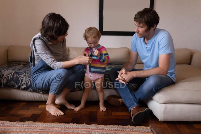 Фронт вид молодых кавказских отца и матери, одевающих своего ребенка — стоковое фото