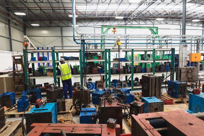 Задний вид молодого афроамериканского рабочего-фабриканта, осматривающего оборудование на складе на перерабатывающем заводе, с полками деталей и оборудования на переднем плане и рядом с ним — стоковое фото