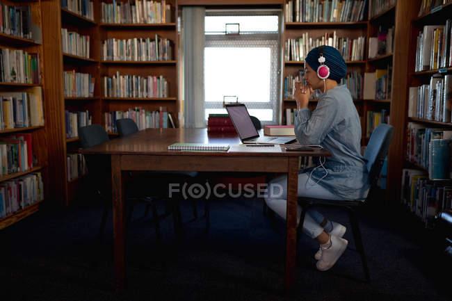 Vista laterale di una giovane studentessa asiatica con turbante e cuffie, che usa un computer portatile e studia in una biblioteca — Foto stock