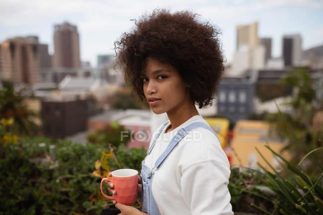 Портрет крупным планом молодой женщины смешанной расы, стоящей на балконе в городе, держа чашку кофе и поворачивая голову, чтобы посмотреть в камеру — стоковое фото