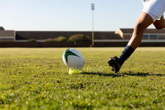 Погляньте на низьку частину жіночого регбі-гравця, який біжить до м'яча, щоб зробити нокаут — стокове фото