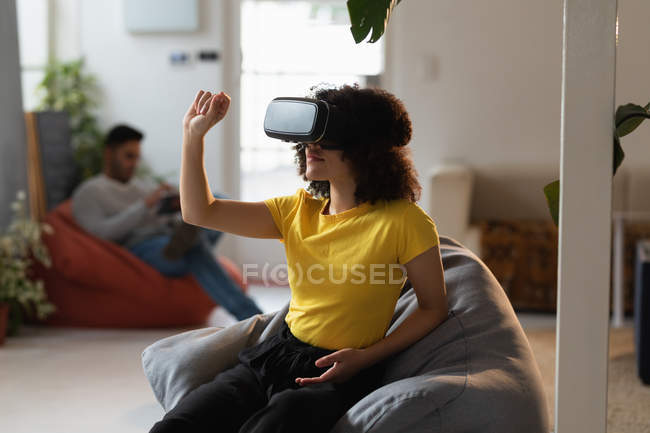 Front view of a young mixed race woman using a VR headset and a young mixed race man sitting in the background at a creative office — Stock Photo