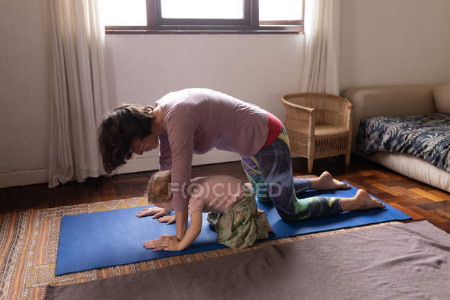 Side view of a young Caucasian mother in a yoga pose next to her baby — Stock Photo