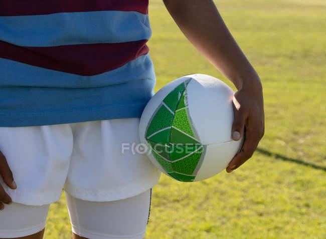 Передня частина жіночого регбі-гравця стоїть на регбі, тримаючи регбі м'яч. — стокове фото