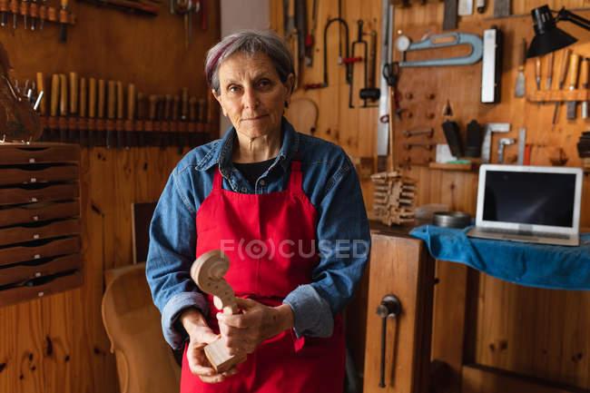 Retrato de uma mulher caucasiana sênior luthier segurando o pergaminho de um violino em sua oficina, com um computador portátil e ferramentas penduradas na parede no fundo — Fotografia de Stock