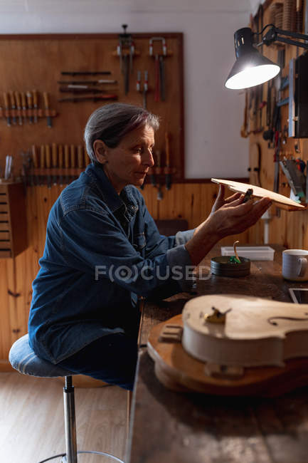 Side view close up of a senior Caucasian female luthier working on the body of a violin in her workshop, with tools hanging up on the wall in the background — Stock Photo