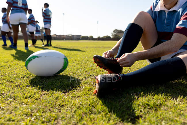 Basso angolo sezione bassa di un giovane adulto razza mista giocatore di rugby femminile seduto e legando il suo stivale su un campo da rugby, con la palla accanto a lei — Foto stock