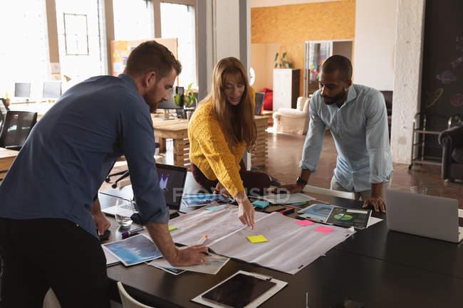 Vista laterale di un giovane uomo afroamericano e di un giovane uomo e donna caucasici in piedi e appoggiati a una scrivania che lavorano insieme su un progetto in un ufficio creativo — Foto stock