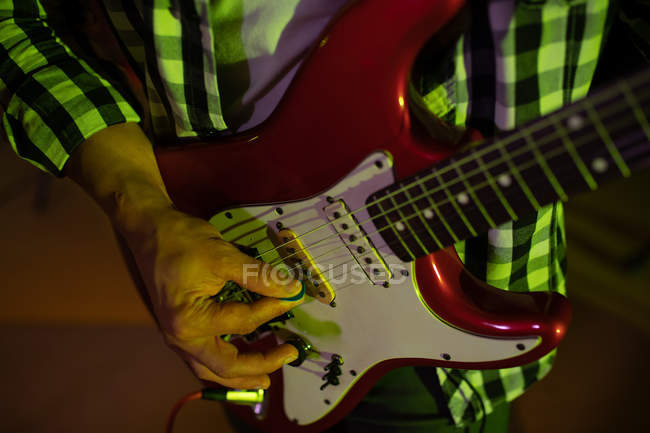 Front view mid section of man playing an electric guitar during a session at a recording studio — Stock Photo