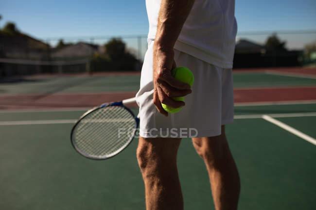 Seitenansicht von Mann beim Tennisspielen an einem sonnigen Tag mit Schläger und Bällen — Stockfoto
