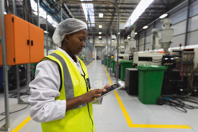 Side view close up of a young African American female factory worker standing using a tablet computer in a warehouse at a processing plant — Stock Photo
