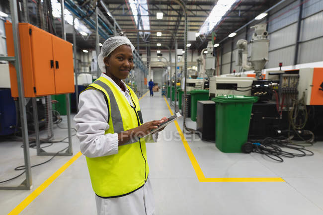 Side view close up of a young African American female factory worker standing using a tablet computer and smiling to camera in a warehouse at a processing plant — Stock Photo