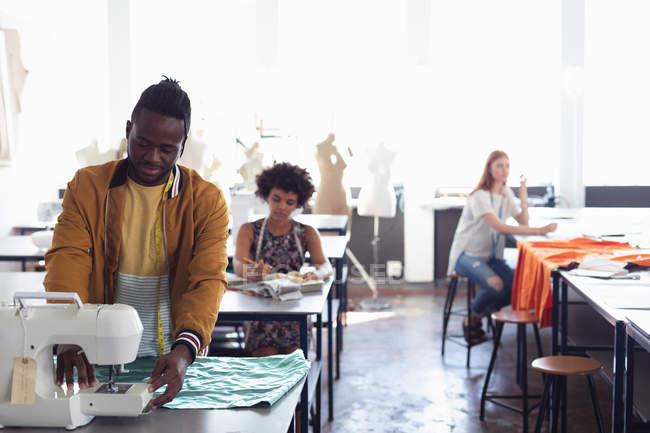 Vista frontal de un joven estudiante afroamericano de moda usando una máquina de coser mientras trabaja en un diseño en un estudio de la universidad de moda, con otros estudiantes en el trabajo de fondo - foto de stock