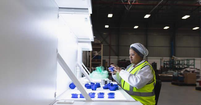 На стіні вимальовується молода афроамериканська працівниця фабрики, яка сидить і перевіряє пластикові деталі під яскравим світлом на складі на заводі. — стокове фото