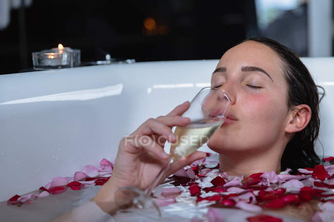 Front view close up of a young Caucasian brunette woman lying in a bath with a lit candle on the side and rose petals in it, drinking champagne with her eyes closed — Stock Photo