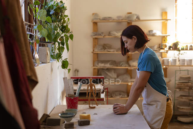 Side view of a young Caucasian female potter standing at a work table and kneading a piece of clay in a pottery studio — Stock Photo