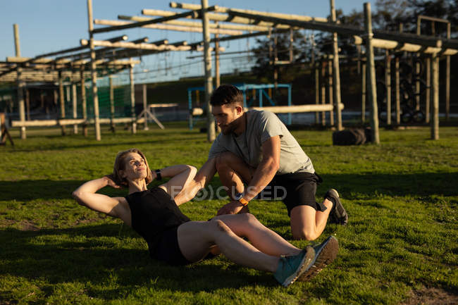 Side view of a young Caucasian woman doing sit ups helped by a young Caucasian man at an outdoor gym during a bootcamp training session — Stock Photo