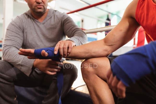 Vorderseite Mittelteil eines jungen kaukasischen männlichen Boxers in einem Boxring, dessen Hände von einem kaukasischen männlichen Trainer mittleren Alters umwickelt werden — Stockfoto
