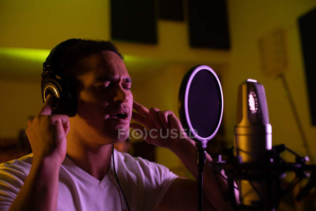 Side view close up of a young mixed race male singer wearing headphones and singing in front of a microphone in a recording studio, with his eyes closed — Stock Photo