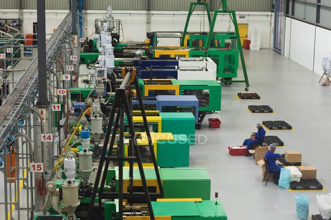 Vue en angle élevé de deux jeunes travailleurs afro-américains de l'usine d'emballage des produits dans des boîtes pour l'expédition dans un entrepôt dans une usine de transformation — Photo de stock