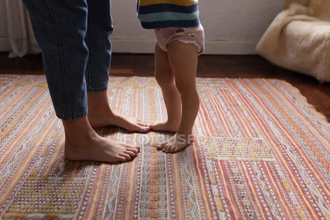 Seitenansicht einer Mutter, die mit ihrem Baby auf einem Teppich steht — Stockfoto