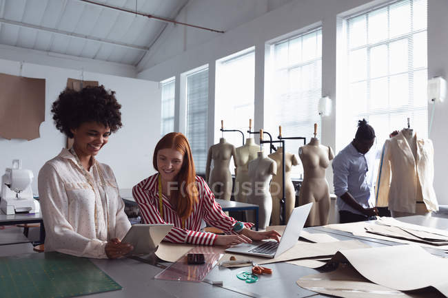 Front view of a young African American female student holding a tablet computer and showing it to a young Caucasian female student using a laptop computer in a studio at fashion college, with a male student working on a jacket in the background — Stock Photo