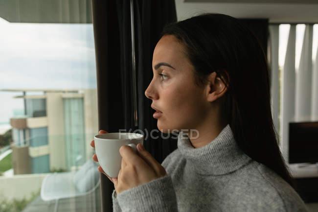 Vue de côté gros plan d'une jeune femme brune caucasienne portant un pull à col roulé gris, regardant par la fenêtre tenant une tasse de café, bâtiments visibles en arrière-plan — Photo de stock
