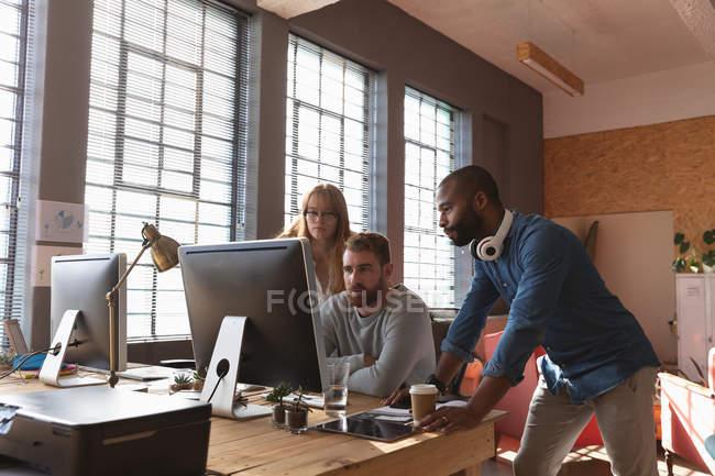 Vista frontal de un joven afroamericano y una joven mujer caucásica de pie a cada lado de un joven colega caucásico sentado en un escritorio usando computadora, mirando a su monitor juntos y hablando en una oficina creativa - foto de stock