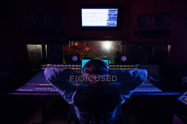 Rear view of a young Caucasian male sound engineer sitting with his hands behind his head at a mixing desk in a recording studio watching the musicians in the recording room through a window — Stock Photo