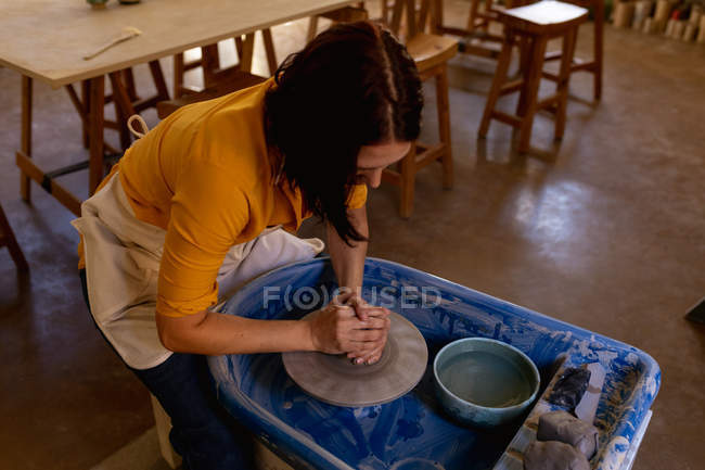Elevated view of a young Caucasian female potter sitting and working with clay on a potters wheel in a pottery studio — Stock Photo