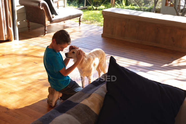 Side view of a Caucasian pre teen boy embracing a dog in a sitting room — Stock Photo