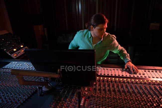 Вид спереди на молодого кавказского звукоинженера, сидящего и работающего за микшерским столом в студии звукозаписи, управляющей фадером канала — стоковое фото