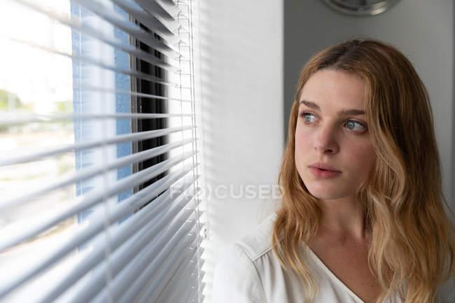 Вид спереди на молодую кавказскую женщину, стоящую с головой и выглядывающую из окна с венецианскими жалюзи в современном офисе креативного бизнеса — стоковое фото