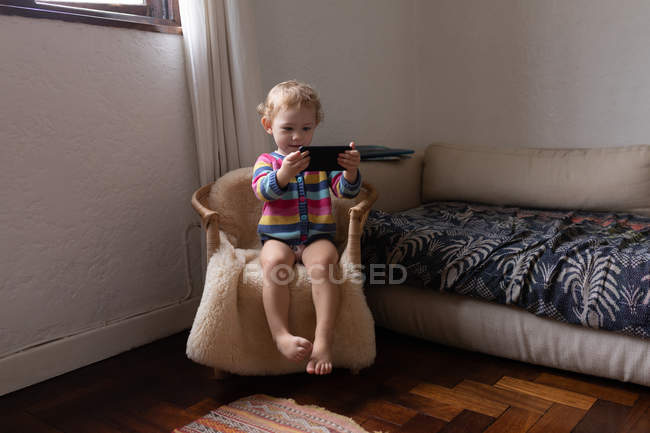 Front view of a Caucasian baby sitting in a chair and holding a smartphone, barefoot — Stock Photo