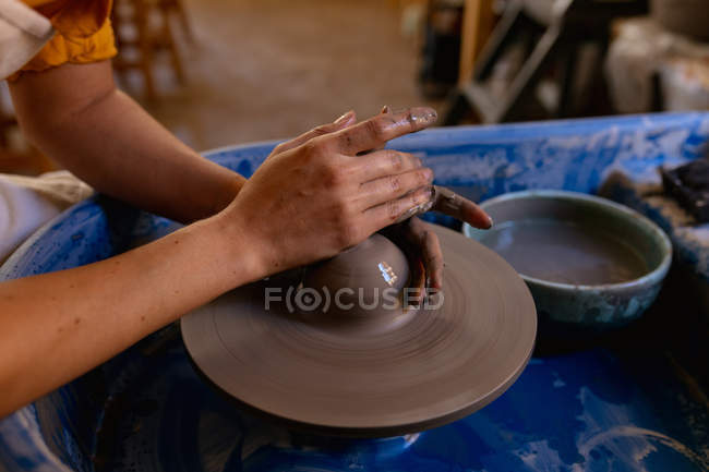 Close up of the hands of female potter shaping wet clay on a potters wheel in a pottery studio — Stock Photo