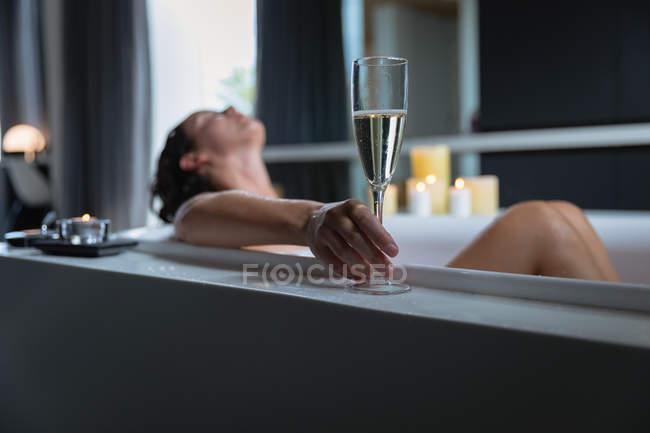 Vista lateral de una joven morena caucásica tumbada en un baño con velas encendidas en el costado, inclinada hacia atrás y sosteniendo una copa de champán - foto de stock