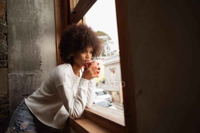 Вид сбоку на молодую расистку, прислонившуюся к подоконнику и выпившую чашку кофе. — стоковое фото