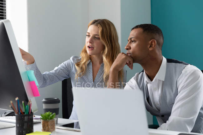 Side view close up of a young African American man using a laptop computer listening to a young Caucasian woman talking and pointing to a computer monitor, sitting together at a desk in the modern office of a creative business — Stock Photo