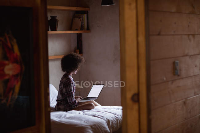 Vista laterale di una giovane donna di razza mista che utilizza un computer portatile seduto sul suo letto a casa, visto riflesso nello specchio nella sua stanza — Foto stock