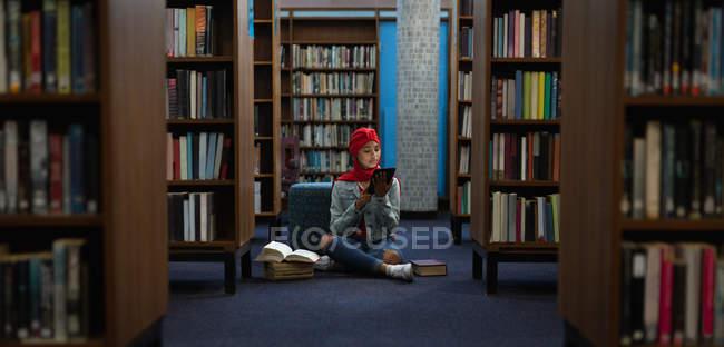 Vista frontale di una giovane studentessa asiatica che indossa un turbante usando un tablet e studia in una biblioteca — Foto stock