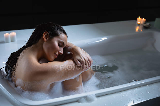 Side view close up of a young Caucasian brunette woman sitting in a foam bath with lit candles on the side, holding her drawn up legs and resting her head on her arms with eyes closed, smiling — Stock Photo