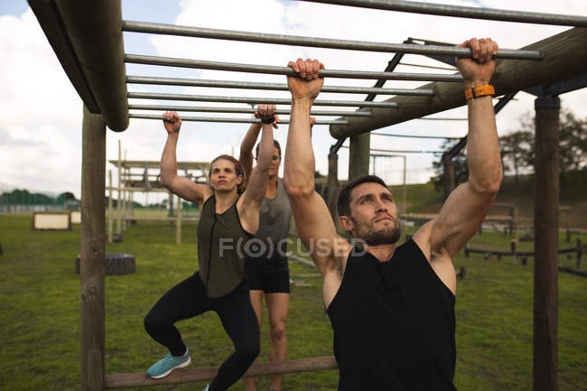 Вид спереди на молодого кавказца и молодую кавказку, висящую в обезьяньих барах во время тренировочного лагеря на открытом воздухе, с другим участником, также висящим на барах на заднем плане — стоковое фото