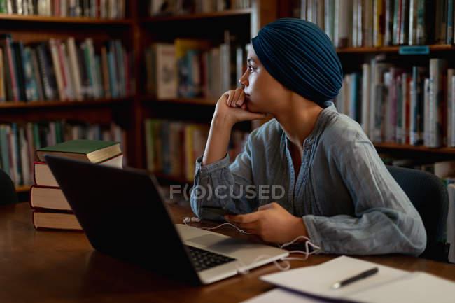 Бічний вид на юну азіатську студентку, яка носить тюрбан за допомогою ноутбука і навчається в бібліотеці — стокове фото