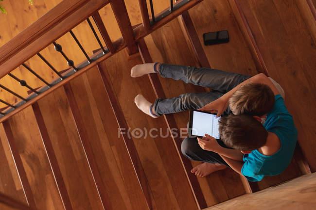 Vista aerea di due ragazzi caucasici pre-adolescenti seduti su una scala a casa, utilizzando un tablet e uno smartphone — Foto stock