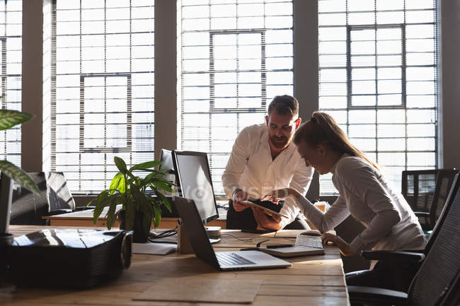 Передній вигляд молодого кавказького чоловіка, який стоїть і розмовляє з молодою кавказькою колегою, що сидить за столом і показує їй планшетний комп'ютер у творчому кабінеті. — стокове фото
