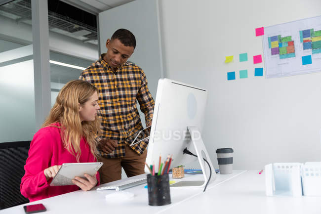 Side view of a young African American man standing and a young Caucasian woman sitting at a desk using tablet computers in the modern office of a creative business — Stock Photo